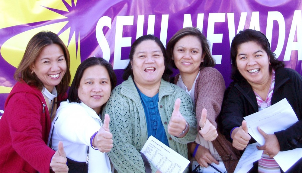 Filipina nurses put their thumbs up after dropping their strike ballots in the box.