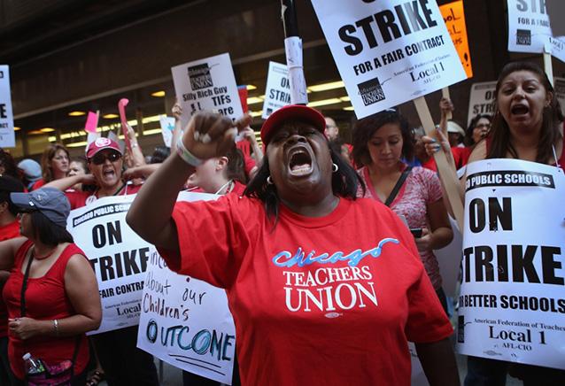 Chicago public school teachers and their supporters picket in front of the Chicago Public Schools headquarters