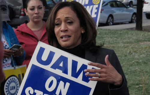 Kamala Harris talks to striking workers after walking a picket line with UAW member