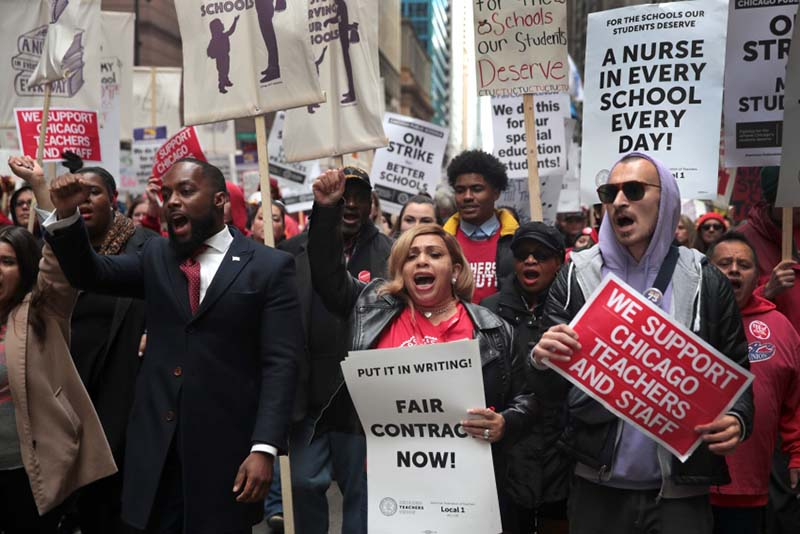 Striking Chicago public school teachers and their supporters march through the Loop