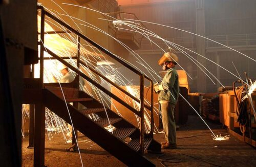 A worker is surrounded by sparks from molten steel flowing into casts at the TAMCO steel mini mill