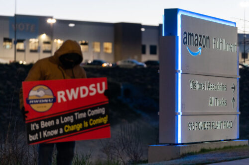 An RWDSU union rep holds a sign outside the Amazon fulfillment warehouse